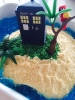 The cake was super-easy, I just baked a round vanilla butter cake, then iced it, sprinkled it with blended up shortbread biscuits for sand,  dessicated coconut for grass with green food colouring and blue jelly for the ocean. A stress-ball Tardis and some old Playmobil foliage completed the look.