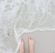 My feet on the white sand.